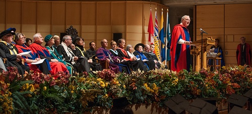 At the podium, the Honorable Paul Martin addresses students, staff, faculty and community members, as members of the UBC President's Office, senior leadership and Education faculty look on.