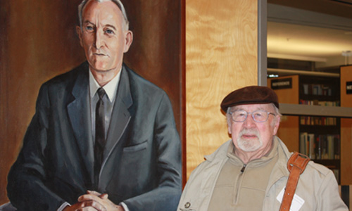 Photo: Professor Sinclair Healy poses with portrait of Dean Neville Scarfe, which he painted.