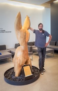 """Artist Dave Robinson stands beside """"Dancing Flames."""""""